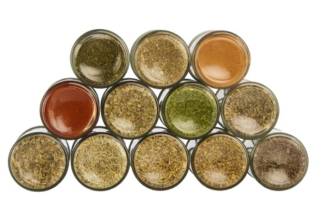 Bottles of colorful spices on white background photo