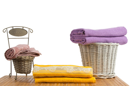 Wicker baskets full of clean colored towels on a wooden table, on white background photo