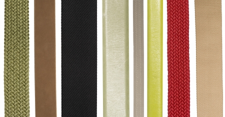 Closeup of various leather and fabric belts isolated on white background photo