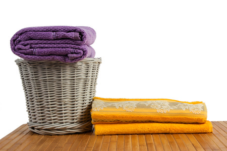 Wicker basket full of clean colored towels on a wooden table, on white background photo