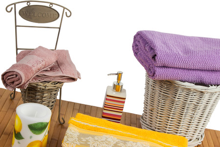 Wicker basket full of clean colored towels on a wooden table in a bathroom set photo