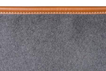 grey rug: detail of sewn beige leather binding on grey rug