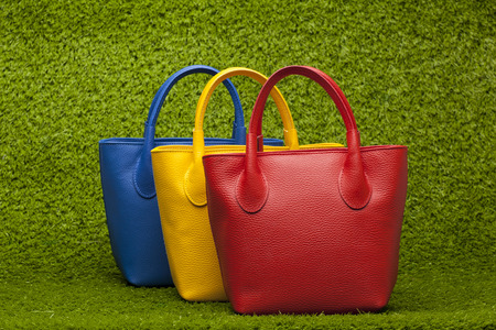 red, yellow and blue purses on green grass photo