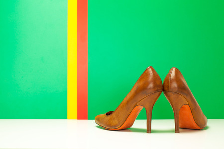 pair of brown high heels on green and stripes background photo