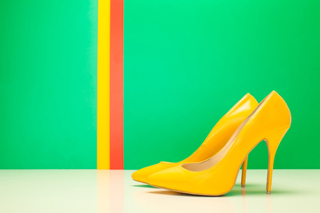 pair of yellow high heels on green and stripes background photo