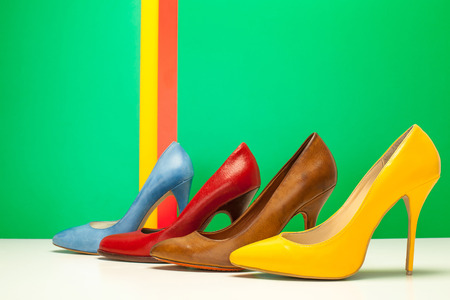for different color of high heels on green background photo