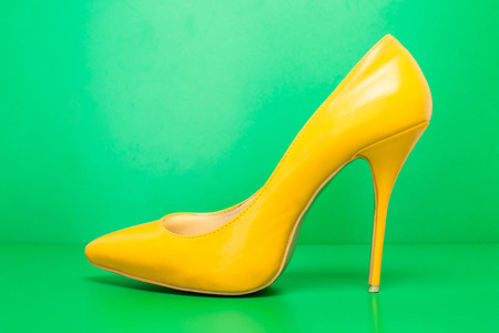 singel yellow high heels on green background photo