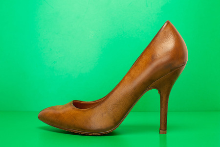 singel brown high heels on green background photo