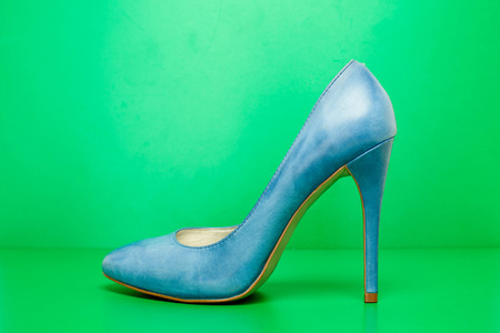 singel blue high heels on green background photo