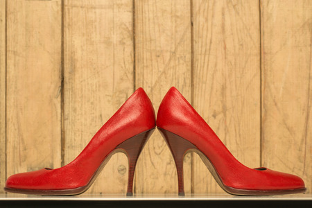 pair of red high heels on old wood background photo