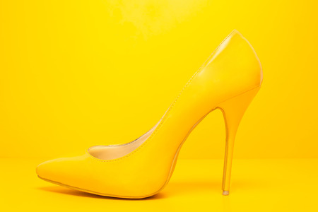 side view of high heels shoes on yellow background photo