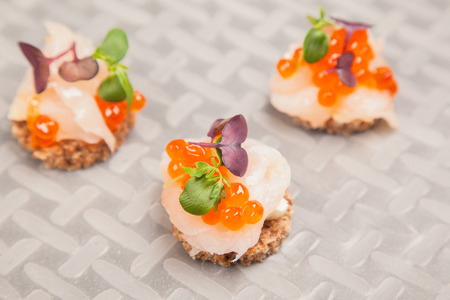 Appetizer of Salmon eggs, fish, and green herbs canapes photo
