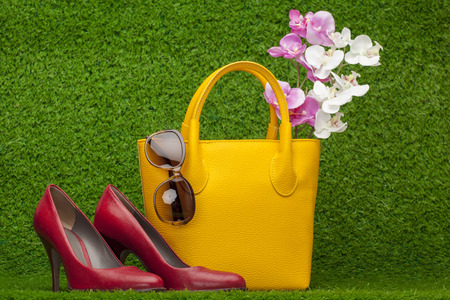 red purse: sunglasses, handbag and red shoes on green grass Stock Photo