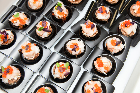 canapes: Appetizer of Salmon eggs, fish, and green herbs canapes
