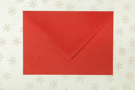 christmastime: closed red envelope on snowflakes background, christmastime