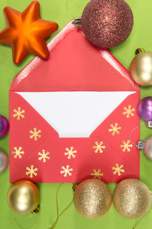 chritmas: red envelope on green background and chritmas ball, christmastime