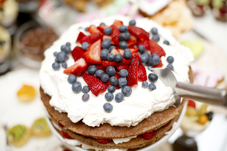 sweet table: Delicious biscuit cake with strawberries and blueberries on sweet table for wedding party