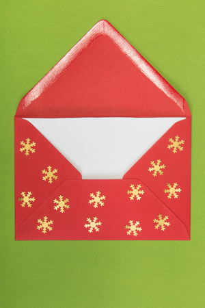 christmastime: opened red envelope and snowflakes on green background, christmastime