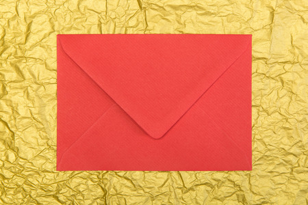 christmastime: red envelope and on golden background, christmastime