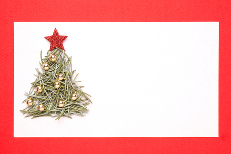 pine needles: Blank Christmas card or invitation with christmas tree made from pine needles on red background Stock Photo