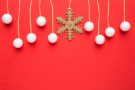 red snowflake background: christmas card with hanging decor on red background