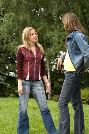 two young girl standin in park photo