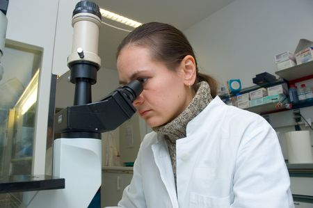 a scientist woman works with microscope in the laboratory
