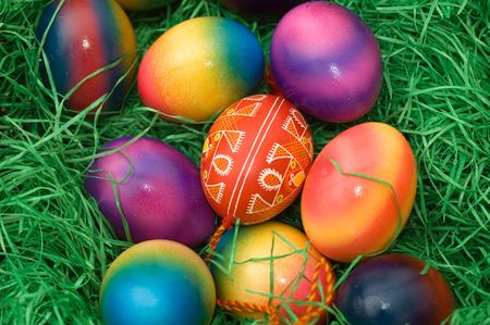 several colored easter eggs laying on the green grass photo