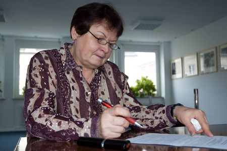 elderly woman in business outfit with pen and glasses Banco de Imagens