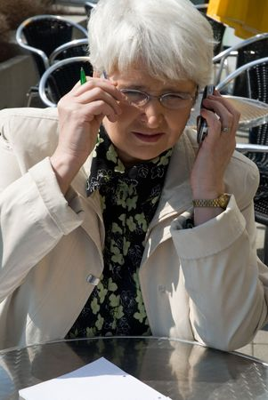 elderly business woman with cell phone photo