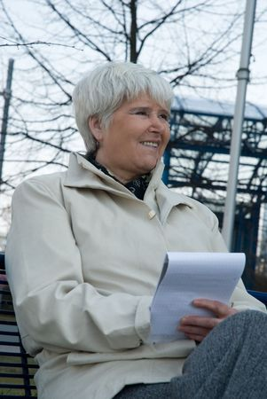 elderly woman in white coat sittin on bench with notepad photo