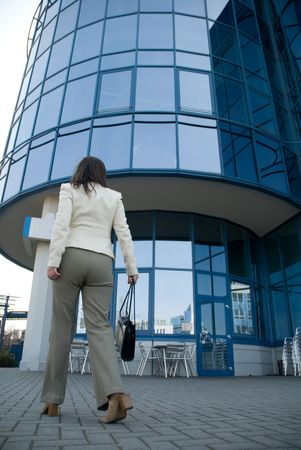 business woman with bag and mobile phone walking in front of skyscraper photo