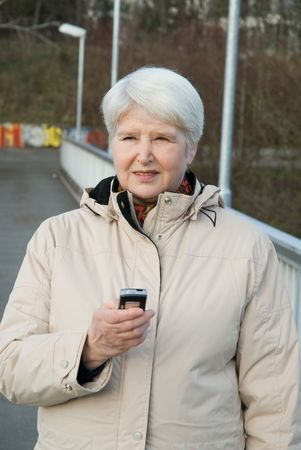 elderly woman outdoors with cell phone