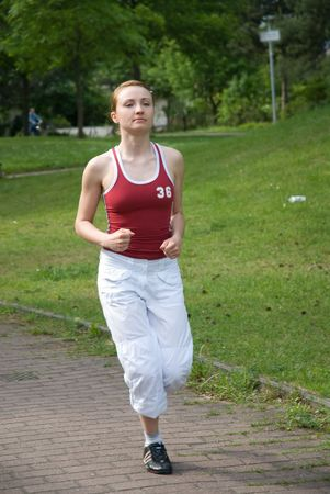 young beautiful girl does jogging in park