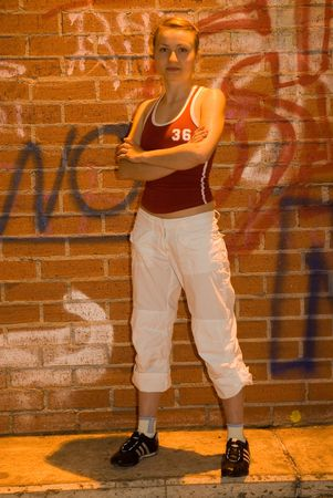 troublemaker: young pretty girl in sport clothes in front of dirty street wall
