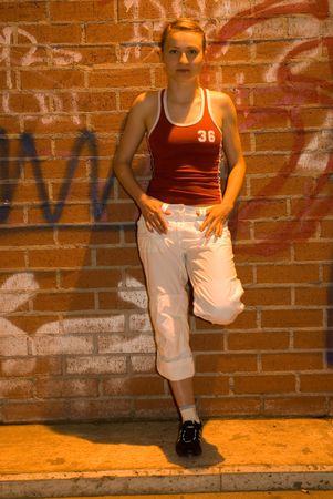 young pretty girl in sport clothes in front of dirty street wall
