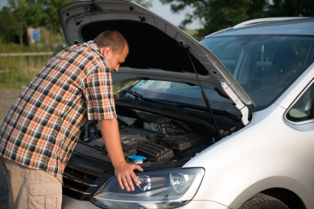 car oil: young man checking broken car