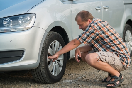 young man checking tire of  siver car photo