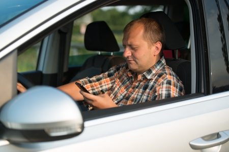Texting and talking while driving, hands of young man on steering wheel photo