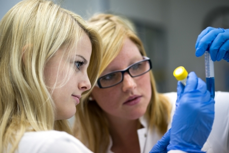 two female scientists working in laboratory with flasks wearing blue gloves