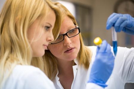 estudiantes medicina: dos mujeres cient�ficas que trabajan en laboratorio con frascos con guantes azules Foto de archivo