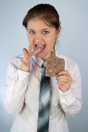 finger licking: young business woman wearing business shirt and tie holding chocolate and licking finger
