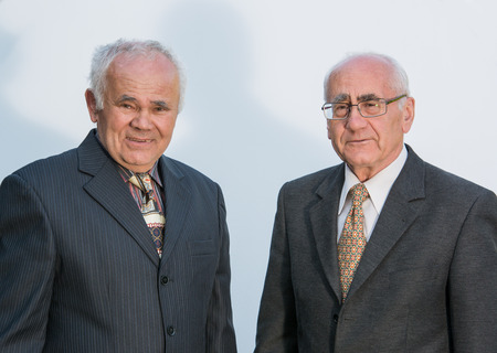 two senior businessmen standing in fron of white background