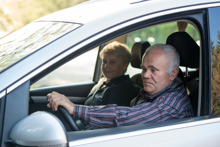 older driver in the car using smartphone, female passenger sitting in the car Banco de Imagens