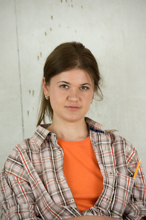 plaid shirt: Attractive woman with pencil in plaid shirt standing in the front  of the wall, planning construction work Stock Photo