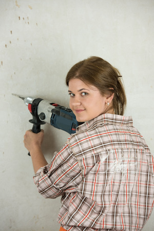 triplet: Blond woman holding electric drill and drilling wall
