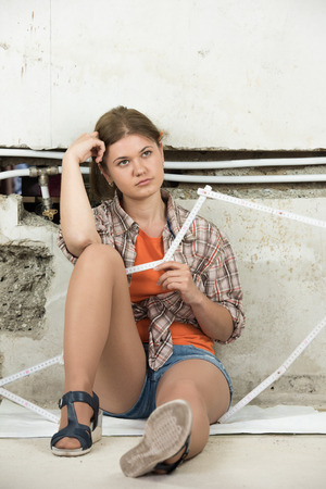 pipe dream: young woman sitting in the front of demolished wall, planning repairing pipeline
