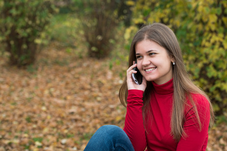 talc: Young woman sitting  and talking on mobile phone in autumn park, in front of yellow leaves, wearing red pullover Stock Photo