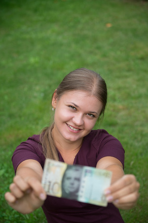 franc suisse: Young happy blonde woman holding Swiss franc banknote Banque d'images