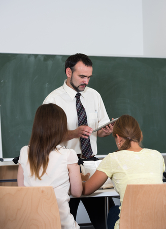 backs: students in the auditorium listening teacher explanation backs to camera